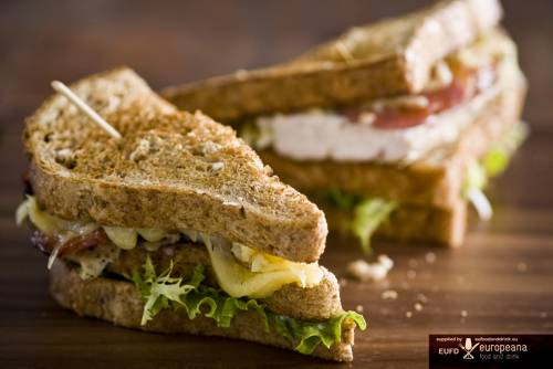 Toasted club sandwich with chicken, cheese, tomatoes, and lettuce on brown bread. The sandwich is said to be named after 4th Earl of Sandwich after he frequently called for the easily handled food while entertaining friends.