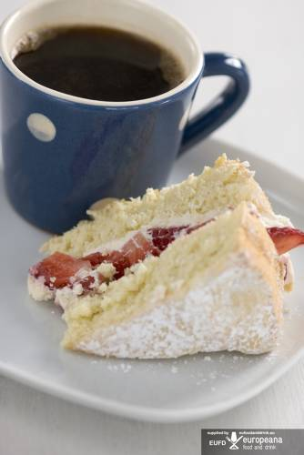 Piece of sponge cake dusted with icing sugar and filled with strawberries and cream on plate with small blue and white spotted mug of black coffee credit: Marie-Louise Avery / thePictureKitchen / TopFoto